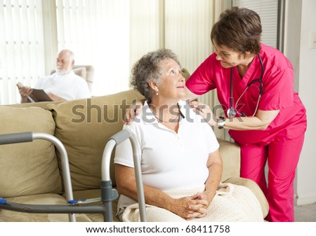 Senior woman in a nursing home, with a caring nurse. - stock photo