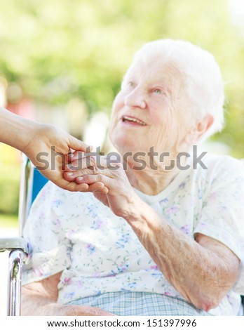 Senior woman in a wheelchair outside holding hands with her caretaker - stock photo