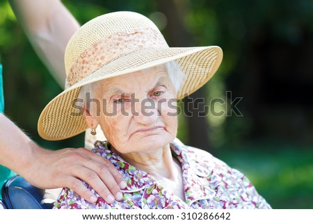 Senior woman in a wheelchair with her caregiver - stock photo