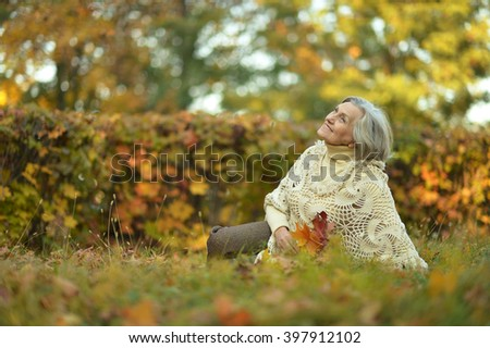 Senior woman in autumn park - stock photo