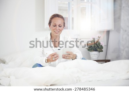 senior woman in bead reading a message on her mobile phone - stock photo