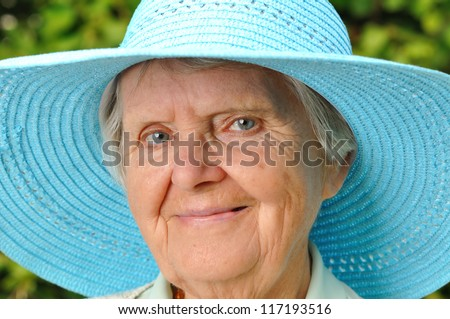 Senior woman in blue hat outdoors in garden. MANY OTHER PHOTOS WITH THIS SENIOR MODEL IN MY PORTFOLIO. - stock photo