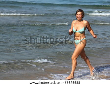 Senior woman In Fitness on the Beach - stock photo