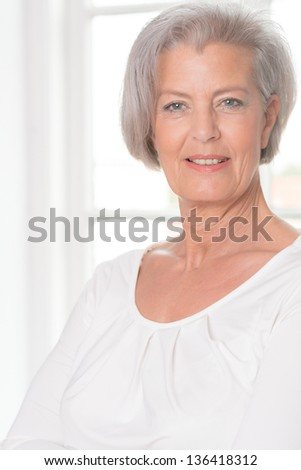 Senior woman in front of a white window - stock photo