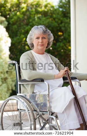 Senior woman in her wheelchair at home - stock photo