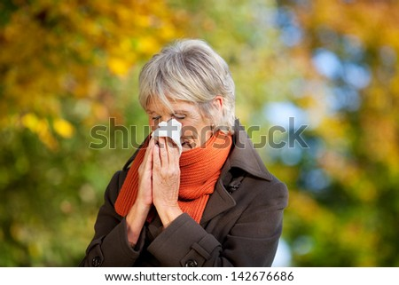Senior woman in jacket suffering from cold in park - stock photo