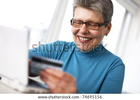senior woman in living room using laptop  holding credit card and smiling - stock photo
