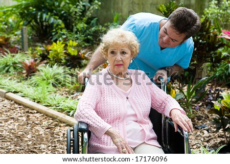 Senior woman in nursing home is feeling depressed and forgotten.  Her orderly tries to comfort her. - stock photo