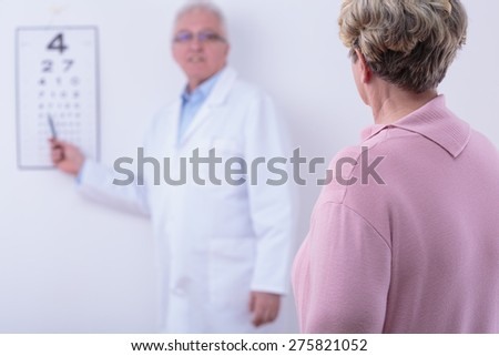 Senior woman in optician's office having examination done - stock photo