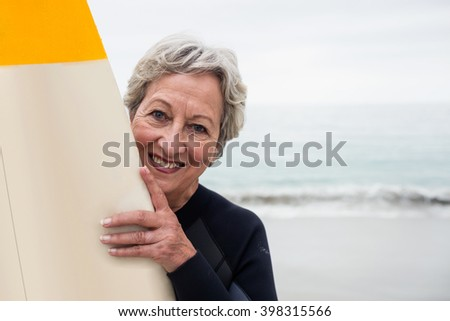 Senior woman in wetsuit holding a surfboard on the beach on a sunny day - stock photo