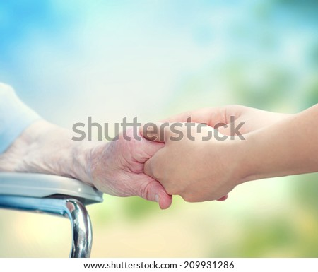 Senior woman in wheel chair holding hands with young caretaker - stock photo