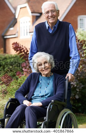 Senior Woman In Wheelchair Being Pushed By Husband - stock photo