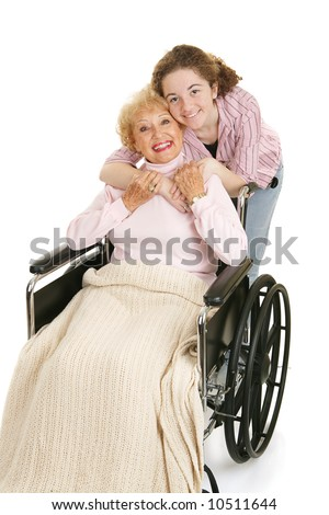 Senior woman in wheelchair gets hug from her teen granddaughter.  Isolated on white. - stock photo