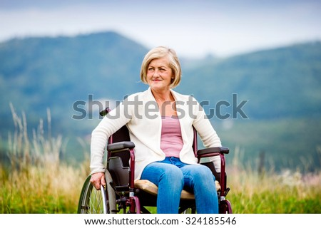 Senior woman in wheelchair outside in nature - stock photo