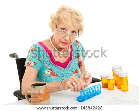 Senior woman in wheelchair sorting her weekly medications.  White background.