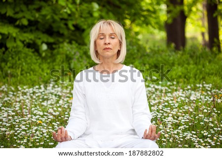 senior woman in white meditating in the forest - stock photo