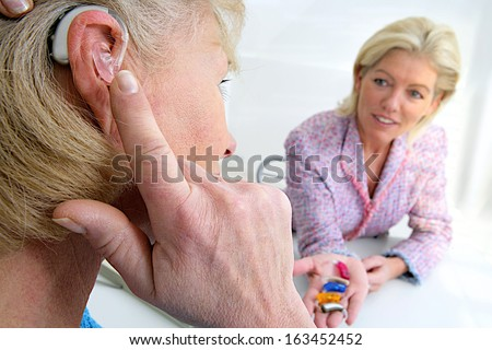 senior woman inserting a hearing aid in her hear. Focus on the colored hearing aid in specialist's hand - stock photo