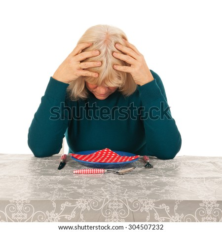 Senior woman is eating alone - stock photo