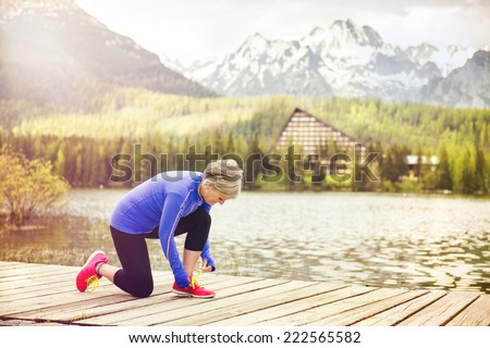 Senior woman is getting ready jogging round the tarn in beautiful mountains, hills and hotel in background - stock photo