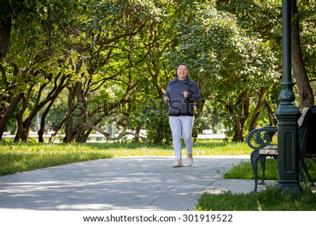 Senior woman jogging in green beautiful park. Healthy lifestyle