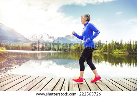 Senior woman jogging round the tarn in beautiful mountains, hills and hotel in background - stock photo