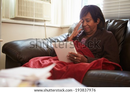 Senior Woman Keeping Warm Under Blanket With Photograph - stock photo