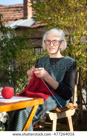 Senior woman knitting with red wool outdoors
