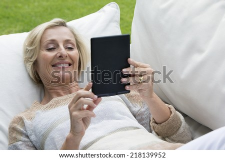 Senior woman laying on outdoor sofa and using digital tablet - stock photo
