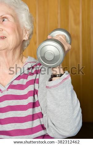 Senior woman lifting dumbbells - stock photo