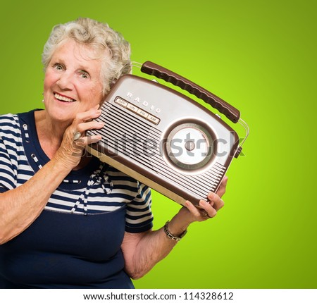 Senior Woman Listening Music On Radio Isolated On Green Background