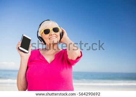 Senior woman listening music with headphone on the beach