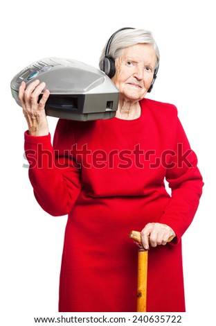 Senior woman listening to music while carrying stereo recorder  - stock photo