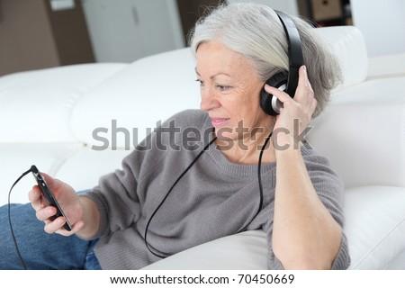 Senior woman listening to music with headphones - stock photo