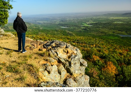 Senior woman looking across the Ozarks of Arkansas landscape from a hiking trail in Mount Magazine State Park .