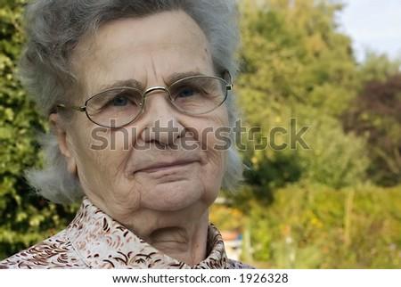 senior woman looking at camera at home - stock photo