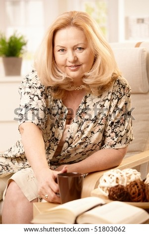 Senior woman looking at camera, smiling, reaching for coffee mug on table, sitting in armchair in living room.