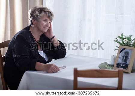 Senior woman looking at dead husband's picture - stock photo