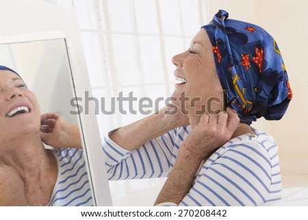 Senior woman looking at mirror and putting her scarf - stock photo