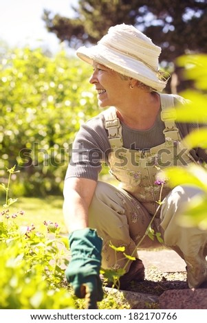 Senior woman looking away and smiling while working in her garden - Outdoors - stock photo