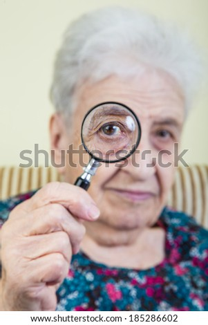 senior woman looking through magnifying glass - stock photo