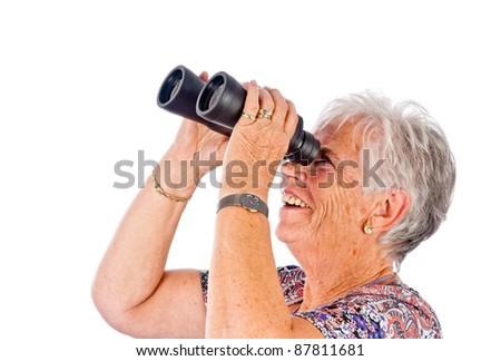 senior woman looks through binoculars - stock photo