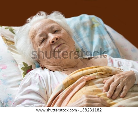 Senior woman lying at bed - stock photo