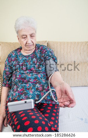 senior woman metering her blood pressure - stock photo