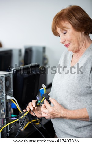 Senior Woman Observing Computer Cables - stock photo