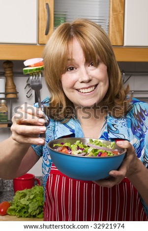 Senior woman offering a healthy salad with love. Focus on her face. - stock photo
