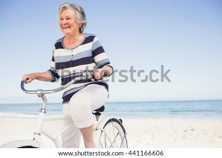 Senior woman on a bike on the beach - stock photo