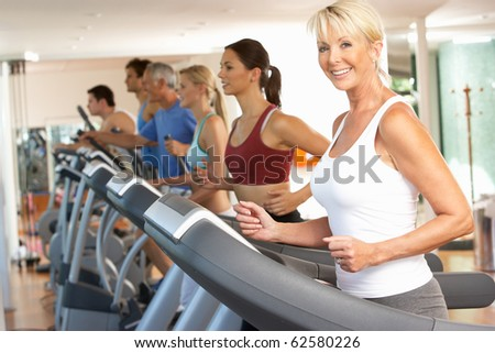 Senior Woman On Running Machine In Gym - stock photo