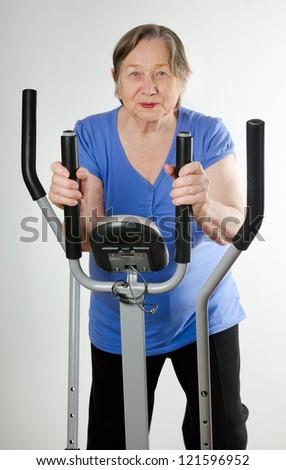 Senior woman on stationary training bicycle - stock photo
