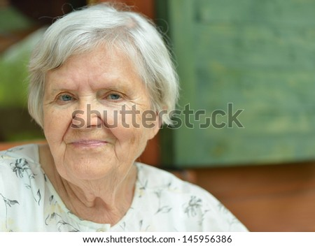 Senior woman on the veranda of his home. MANY OTHER PHOTOS FROM THIS SERIES IN MY PORTFOLIO. - stock photo