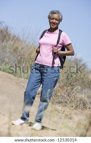 Senior woman on walk in countryside - stock photo